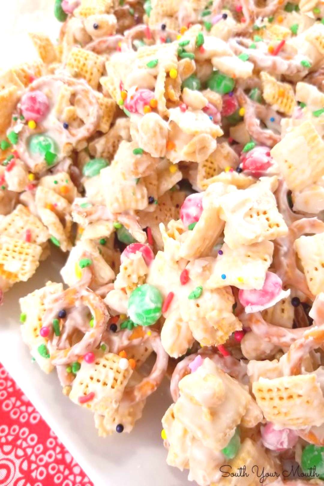 A sweet and salty snack mix made with chex cereal, pretzels, peanuts and M&M's coated with white